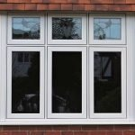 High quality timber effect traditional flush style casement bay windows encapsulating original coloured leaded toplights